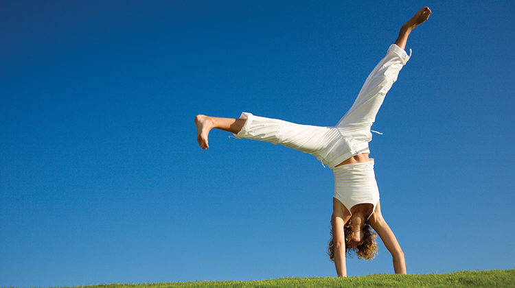 Young woman doing cartwheel on grass